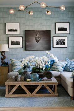 canapé avec coussins décoratifs bleus, fleurs sur la table basse en palettes en bois