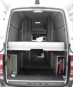 Interior of Peter's super-high-roof Sprinter camper van, showing the electric bed in lowered position.