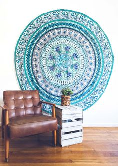 Top off your bed or accent a wall with this unique round tapestry, featuring a bold blue and green mandala pattern on soft white fabric, finished with a pom-pom edge on its border. This tapestry also