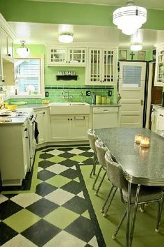 Fabulous green kitchen.  Love the glass-front cabinets, the linoleum floor and the formica and chrome table