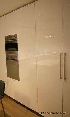 """This kitchen designed by Daniel Popescu of Bilotta Kitchens for a downtown Manhattan home features Artcraft cabinetry's Eva channel door in a high gloss polyester. The countertops are pure white quartz and the backsplash is a full slab of ¾"""" pure white Caesarstone. Fully integrated appliances are by Smeg and Liebherr."""