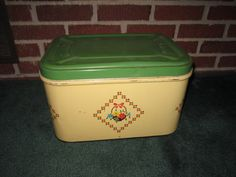 A vintage 1940's metal cream color bread box with a jadeite green lid with a cute water slide decal..