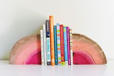 DIY Half Log Book Ends -  Supplies Needed: half a log (can be as thick or thin as you prefer for this project) / paint brush / multicolored paints (pick 3 in the same family if you are going for ombre as pictured here) / sanding block / saw / varnish (optional) for finished product @homedit
