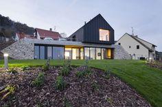 Při pohledu z dálky dům tvarově splývá s okolní zástavbou, přesto klasické venkovské stavení na první pohled zaujme jednoduchou formou s černým pláštěm. Z uliční úrovně by pod čistou linií stavby nikdo nehledal obytné podlaží zahloubené do svažité zahrady. Dvě přes sebe přeložené hmoty objektu vyšly tvořivým způsobem vstříc požadavkům investorů i náročným pravidlům CHKO.