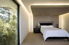 На фото парящий натяжной потолок переходящий на стену в спальне