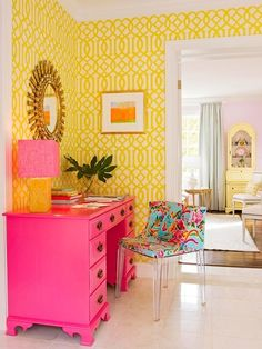 Bright pink desk, yellow trellis wallpaper, with Philippe Starck Mademoiselle Chair