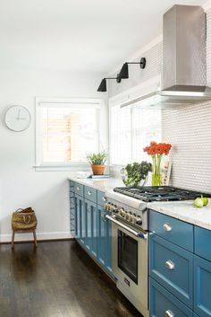 teal cabinets against an all white kitchen is the perfect pop of color.