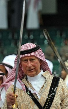 HRH The Prince of Wales, Prince Charles (C), wears a traditional Saudi uniform as he joins a traditional Saudi sword dance, also known as 'Arda' and performed during the Janadriya cultural festival at Der'iya in Riyadh, Saudi Arabia, 18 Feb 2014.