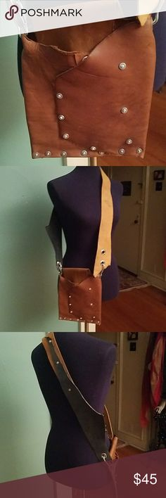 Nittna hand made leather crossbody bag Designer Nittna came from Serbia and ended up in Chicago where she and her partner started their business making fine leather bags. Leather is repurposed. Any marks are either natural or were there when purchased.  See upper part of strap in 2nd photo. Rivets throughout. Strap can be attached on either side of bag, see photos, or removed completely. Body of bag is deep tan and strap is light tan and black. Snap closure hidden under front flap. 21 inch…