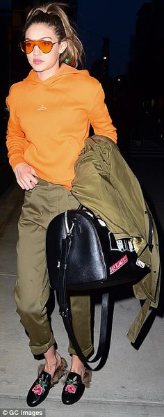 Matchy matchy: Gigi Hadid, 21, matched her orange Mirina Collections sunglasses to her Holzweiler hoodie