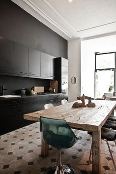 kitchen space that pares the contemporary black cabinetry and bench top with aged weathered floor tiles and a rustic timber table