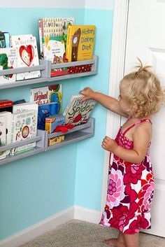 SPICE RACK BOOK SHELVES??? Ikea spice racks make great book shelves. Just line up a few side by side and make a few rows of shelves. Easy reach for your kids and they also have the covers facing out which I love more than a regular book case for kids!