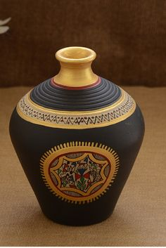 This pot is made of terracotta, brought to you from Uttar Pradesh and decorated with the Warli art, native to the tribals of Maharashtra. It is handpainted with acrylic colours in black and gold. The minimal design on this pot will give a classy appeal to your room.
