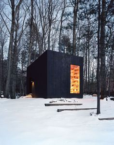"""Tucked away in the quiet woods of Upstate New York, you'll find the Hemmelig Rom, a cozy cabin equipped with its own private library. A bookworm's dream come true, the secluded space—whose name translates to """"secret room"""" in Norwegian—was designed by Studio Padron in collaboration with Smith Design Office."""