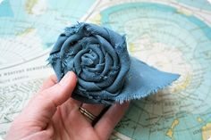 Perhaps you've seen this flower elsewhere : it is a popular one.  There are many different ways to roll and fold the fabric for different looks, but today I'll show how I make these rolled fabric flowers. Here's what you'll need: :: fabric :: scissors :: hot glue gun {you could also hand stitch…