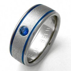 Titanium Wedding Ring Titanium Wedding Ring by Exotica Jewelry - Titanium wedding ring with two blue grooves and sapphire. Finished with pebble-textured center and polished borders. Handcrafted by Chris Titanium Jewelry, Titanium Wedding Rings, Titanium Rings, Black Wedding Rings, Custom Wedding Rings, Fitted Lace Wedding Dress, Sapphire Band, Jewelry Rings, Rings For Men