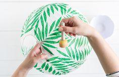 Faça você mesmo: passo a passo para a criação de uma lanterna japonesa com colagem de folhas tropicais.