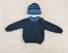 A beautiful hand knitted Baby Boy Sweater and Hat Set.  Knitted in a textured flecked yarn in two shades Charbon (grey) and Denim (blue)