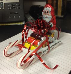 Candy Sleighs: Hot glue gun, 1 Kit Kat bar, 2 candy canes, 6 Hershey bars (stacked 3, 2, 1), 1 Candy Santa, ribbon and a bow on top!