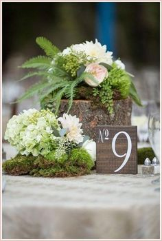 Centrotavola green con fiori, foliage e tronchetti di legno.