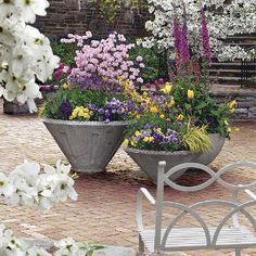 When planning your flowerbeds, buy extra plants for accents. These containers were planted with flowers left over from the borders. Not only do the containers look great, but also they tie back into the colors of the adjacent walk.