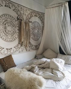 wall tapestry for room with comfy cream coloured and white blankets/pillows.