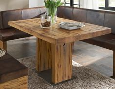 beautiful dining table made of wood and a square leather sofa