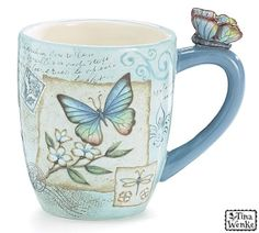Ceramic faint blue mug with decal design of a blue butterfly on torn ivory paper accented by dogwood stem, dragonfly, faint writings and postage marks. Sculpted butterfly on blue handle. Holds 15 oz. Dishwasher and microwave safe.
