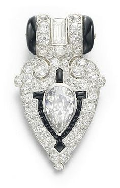 AN ART DECO DIAMOND AND ONYX DRESS CLIP, BY CARTIER Designed as a pierced single and circular-cut diamond geometric plaque, centering upon a pear-shaped diamond, accented by a rectangular-cut diamond and onyx detail, mounted in platinum, circa 1925 Signed Cartier, no. 863153A