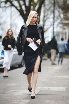 Monochromatic black outfit with a leather jacket and knee length skirt with a slit