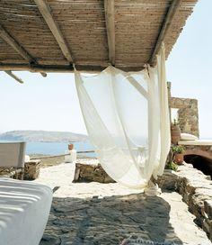 Sous les cannisses, et protégée du soleil par des voiles de coton, la salle à manger outdoor fait face à l'île d'Icare.