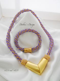 Impressive choker statement necklace braiding using seed beads. The ends are finished off with beaded end caps. The focal point is a brushed gold-toned curved large magnetic clasp.  By Debbie's Designs