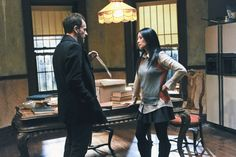 Lucy Liu as Joan Watson on Elementary (color block sweater, pleated skirt, graph paper shirt, tights, boots)