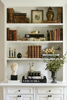 This styled bookshelf features a mix of antique books, striped bookends, vases, and picture frames.