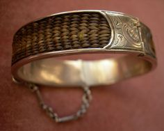 A fine piece of mourning jewelry. Hinged silver bracelet set with braided human hair.