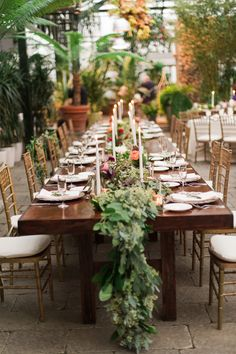 table runner with greenery - photo by Kelly Sweet Photography http://ruffledblog.com/botanical-garden-wedding-with-glass-ceilings #weddingreception #flowers #tablerunner