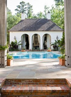 Have 1 center arch (not 3) and keep on same level as pool (no step up) and place long concrete fire pit in front, to be viewed from pool and from pool house.