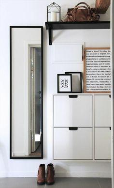 hall d entrée maison avec un miroir haut et étroit et des cases de rangement en blanc