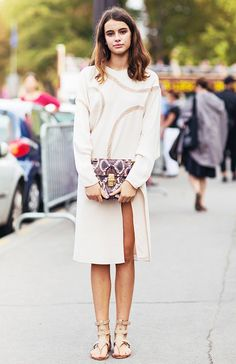 A white dress with sheer paneling is worn with a Chloé snakeskin bag and gladiator sandals