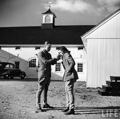 Photo of Gene Tierney and friend Maturin Waldo lighting her cigarette (hey, it was the 40's) behind the stables of the Fairfield County Hunt Club in Westport, CT. by Hart Preston, 1940.