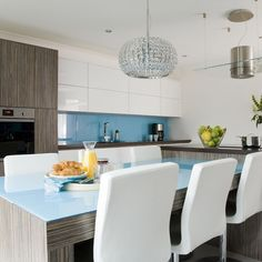 Modern blue kitchen.  The long glass-topped table is perfect for family meals, but is also a stunning focal point. The white gloss units marry perfectly with the vivid blue splashback and tabletop, for a modern look.