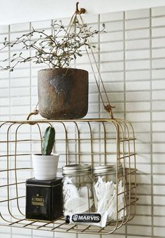 industrial-look retro wire basket turned on its side and suspended from a hook makes a small shelf to stow personal care items in the bath up and off the countertop