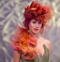 THE ARTIFICIAL APPEARS NATURAL AS VIBRANT REDS MEET THE TENSION BETWEEN A CLASSIC SIDE PONYTAIL AND ORNAMENTAL ROLLS OF HAIR. A DELIBERATELY UNFINISHED YOUTHFUL APPEARANCE #Wella Trend Vision • #Urban Native
