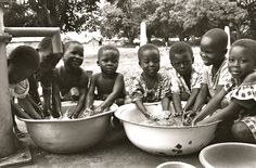 A group of children washing their hands in the washing station in their village. These washing stations are common in most Zambian villages for people to wash their hands after working. The water becomes dirty quickly, so some children are given the job of cleaning and refilling the dishes with well water.