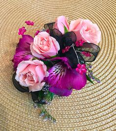 A gorgeous homecoming corsage with pink spray roses,  purple alstroemeria, caspia, pink gems, and a black bow.