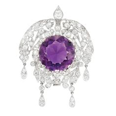 Belle Epoque Platinum, Amethyst and Diamond Pendant The pierced mount of garland motif centering one round amethyst approximately 19.00 cts., tipped by four flexibly-set drop-shaped pendants, set throughout with 98 old-mine cut diamonds approximately 4.00 cts., circa 1910