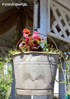 Flower bucket hung by a bracket and spring (from GypsyFarmGirl)