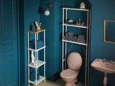 Blåt badeværelse med fritstående hvid reol med tophylde af bambus. Og vægmonteret åben opbevaring over toilettet med toiletartikler og ekstra håndklæder.