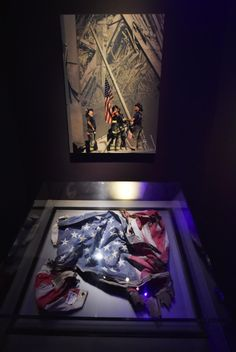 An American flag found in the rubble is displayed under the now iconic image of a flag being raised by firemen at the World Trade Center site by Thomas E. Franklin of The Record.