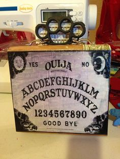 This cigar box purse features an Ouija Board on the front, my signature plastic brass knuckles handle, my signature no nonsense clasp and a built in